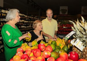 Volunteer assists two members with grocery shopping