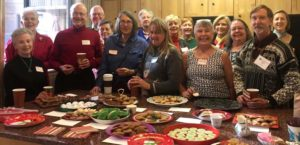 Members and volunteers pose in front of the food table at an ANV pot-luck dinner