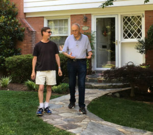 Two men walking in front of a house